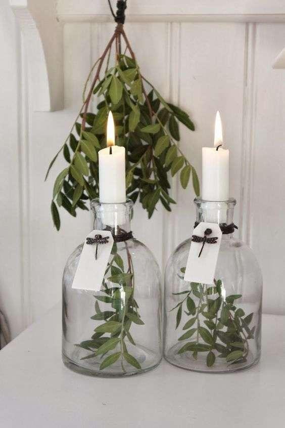 Bougeoirs en bouteilles de récupération et des feuilles à l'intérieur