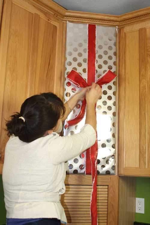 femme-qui-accroche-ruban-rouge-placard-cuisine